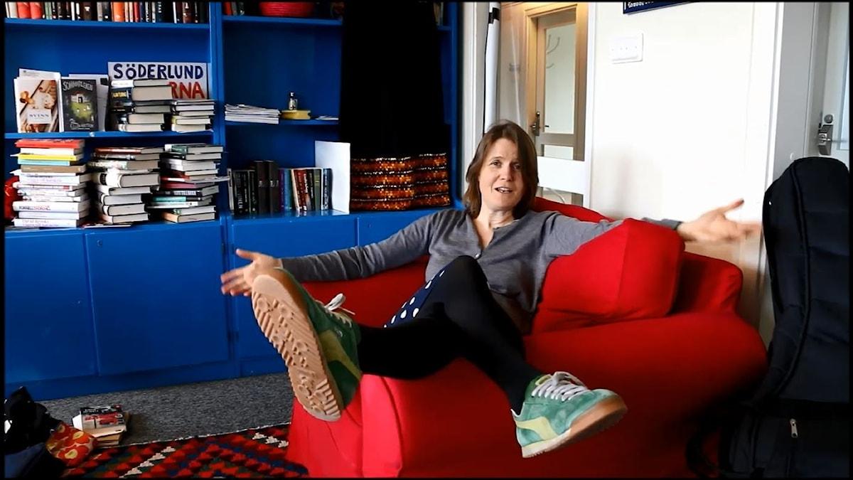 """Louise Epstein sitter i en röd soffa och ställer sig frågan """"Vad förknippar DU med ordet tant"""" vilket hon visar genom att gestikulera med utslagna armar."""