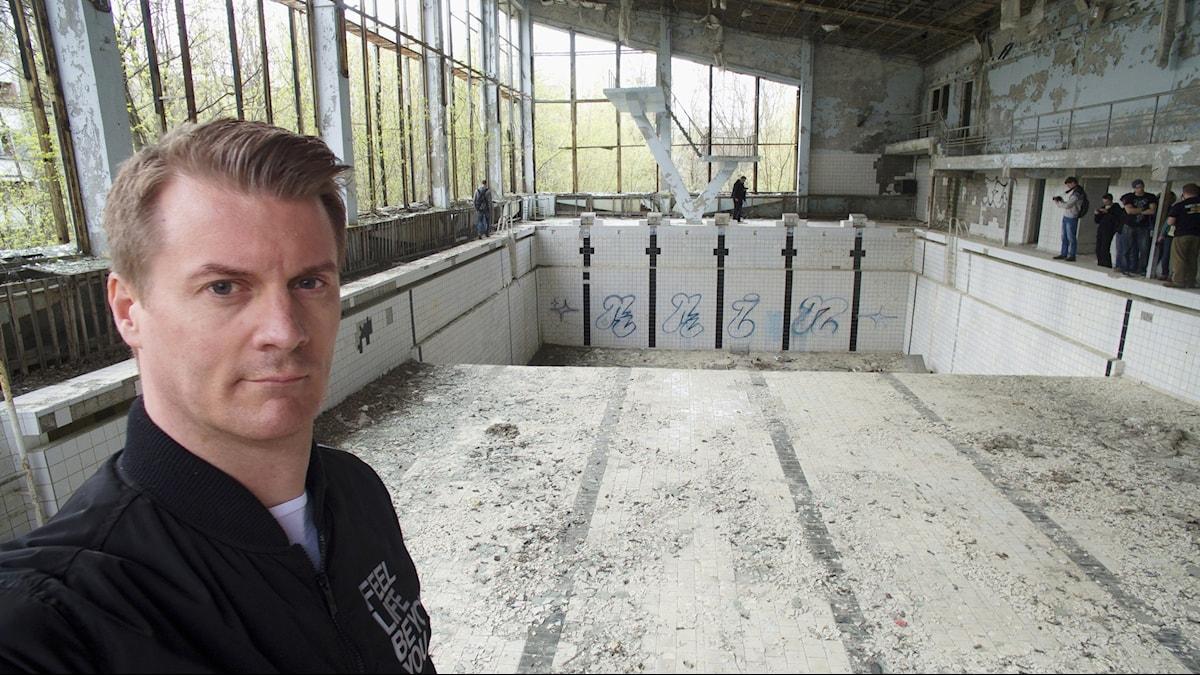 Tobias Carlsson som medverkar i programmet har besökt kärnkraftverket Tjernobyl i staden Pripjat i norra Ukraina. Här står han i det som är kvar av den övergivna stadens simhall.