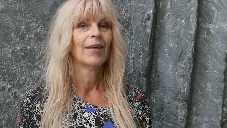 Närbild på Kajsa Grytt som står framför en bergvägg i Radiohuset.