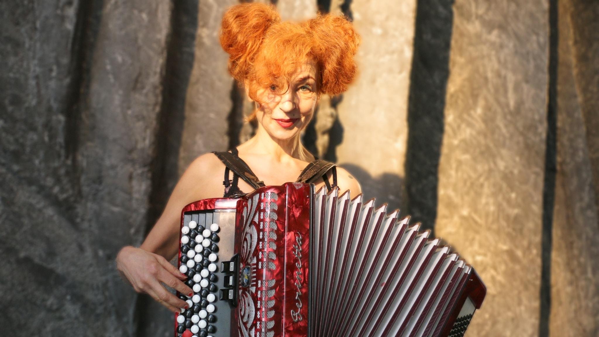 Artisten Marta Oldenburg poserar med sitt dragspel. Hon har stort rött hår och färgen på dragspelet är också röd. Belysningen är dramatisk.