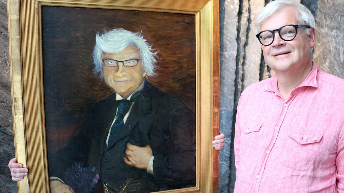 Thomas Nordegren poserar vid sidan av ett porträtt i olja som föreställer honom själv.