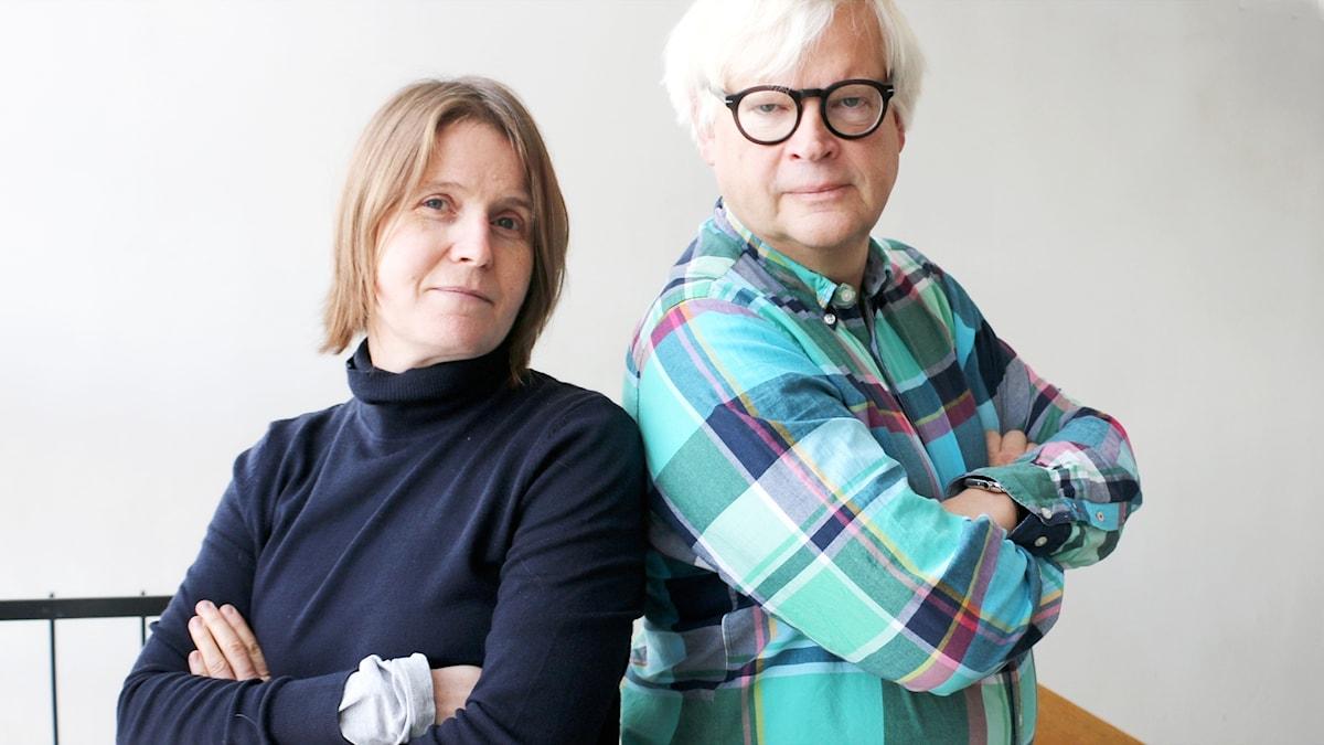 Thomas Nordegren och Louise Epstein står med ryggarna vända mot varandra med armarna i kors och tittar in i kameran.