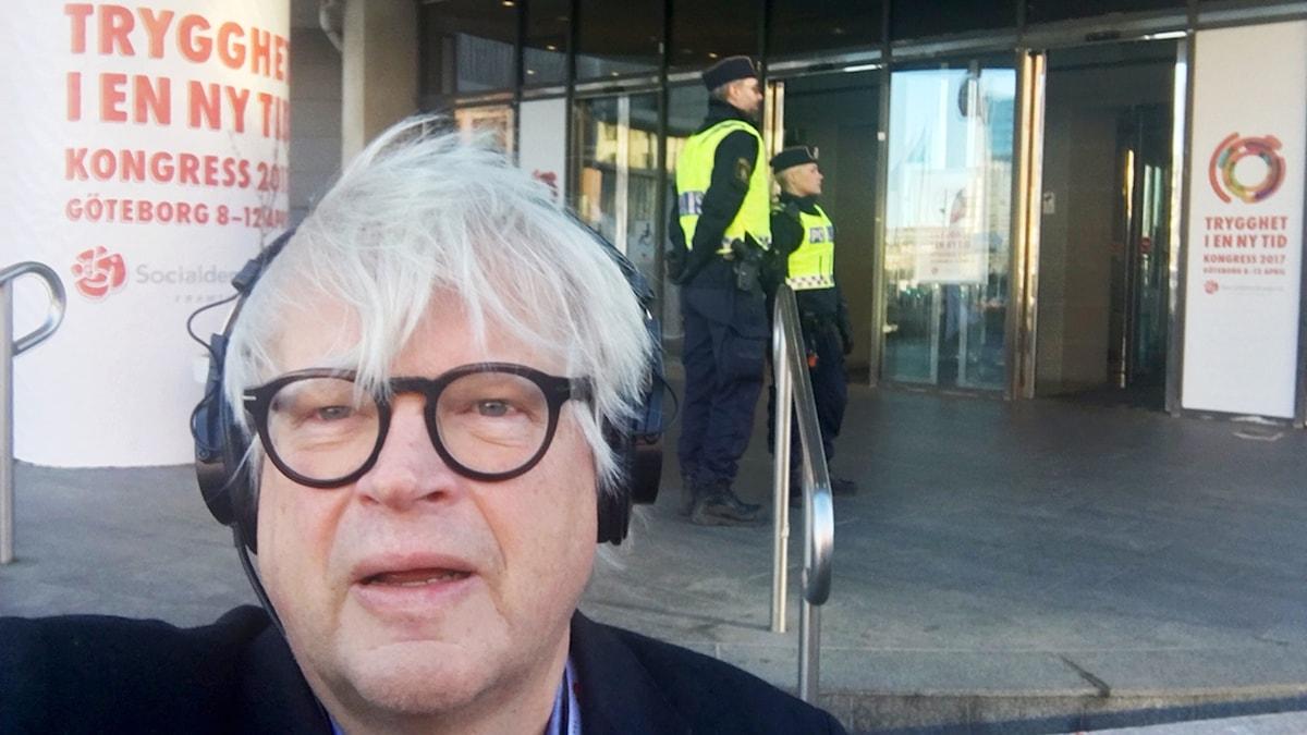 """Thomas Nordegren står framför ingången till Svenska Mässan där S-kongressen pågår. I bakgrunden syns två poliser och en affisch där man ser texten: """"Trygghet i en ny tid, Kongress Göteborg"""" med stora bokstäver."""