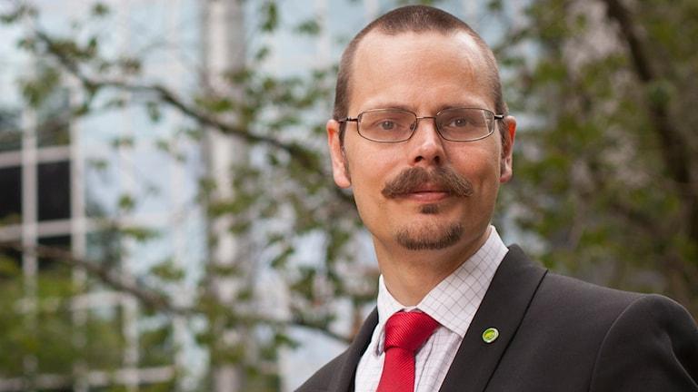 Max Andersson, Miljöpartiet porträtterad med grönska i bakgrunden.