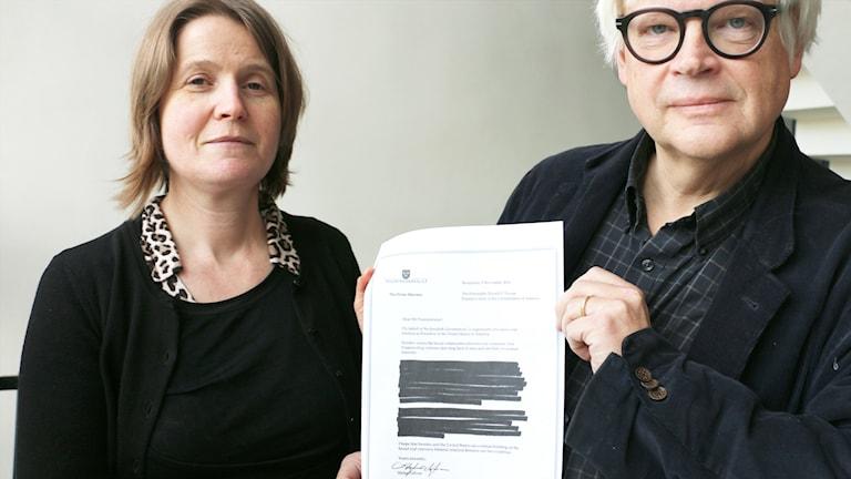 Louise Epstein och Thomas Nordegren håller upp Stefan Löfvens brev till Donald Trump där stora delar är överstrukna.