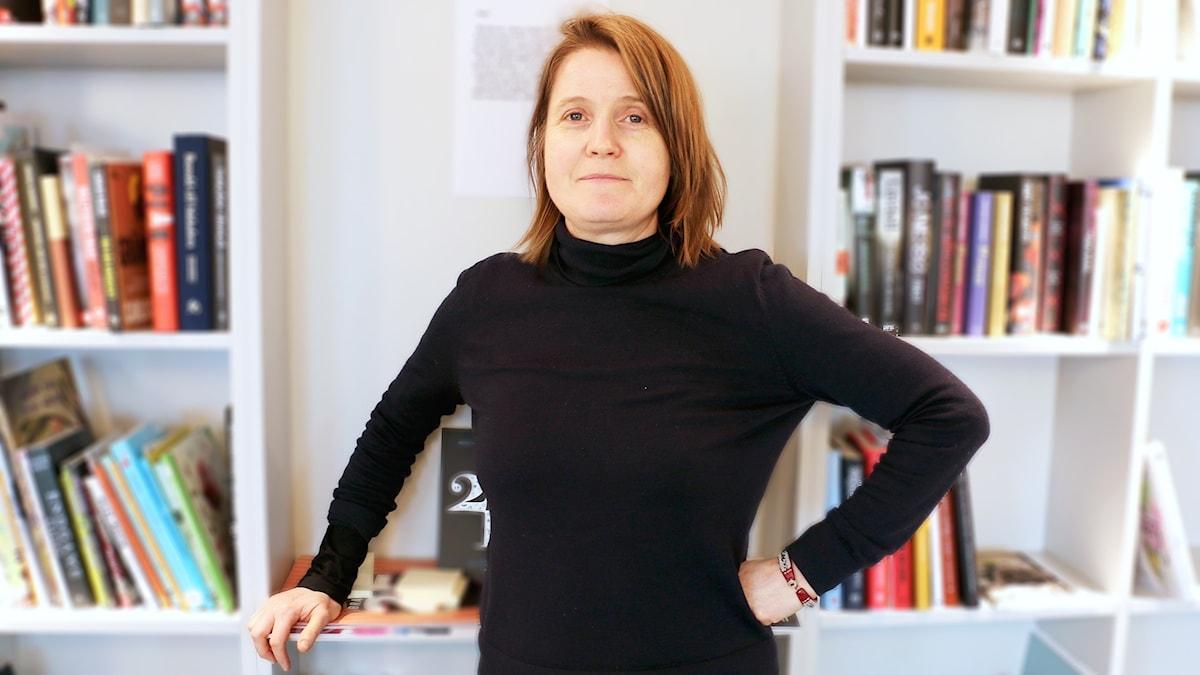 Louise Epstein står framför en bokhylla.