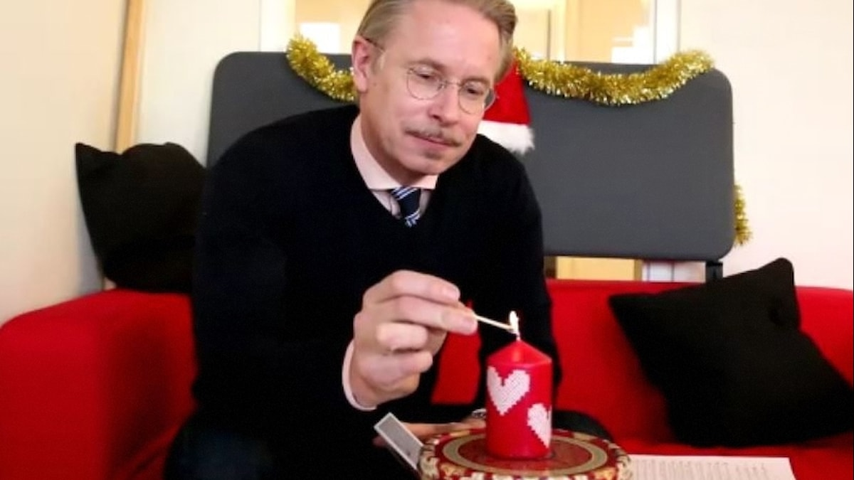 Daniel Alling tänder ett ljus och sitter i en röd soffa med tomtepynt runt sig.