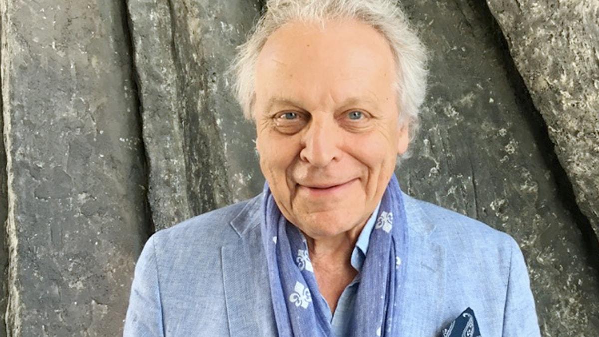 Författaren Herman Lindqvist ler in i kameran. Han är iklädd en ljusblå kavaj.