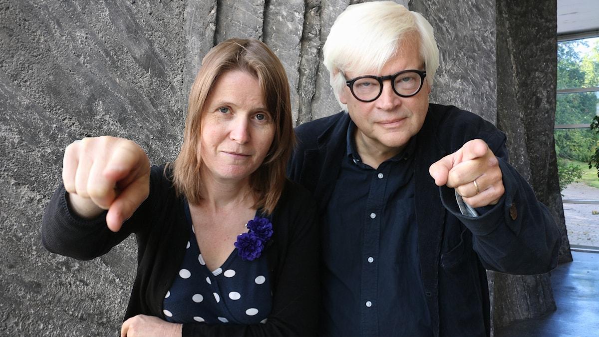 Louise Epstein & Thomas Nordegren pekar mot fotografen och tittar bestämt in i kamernan.
