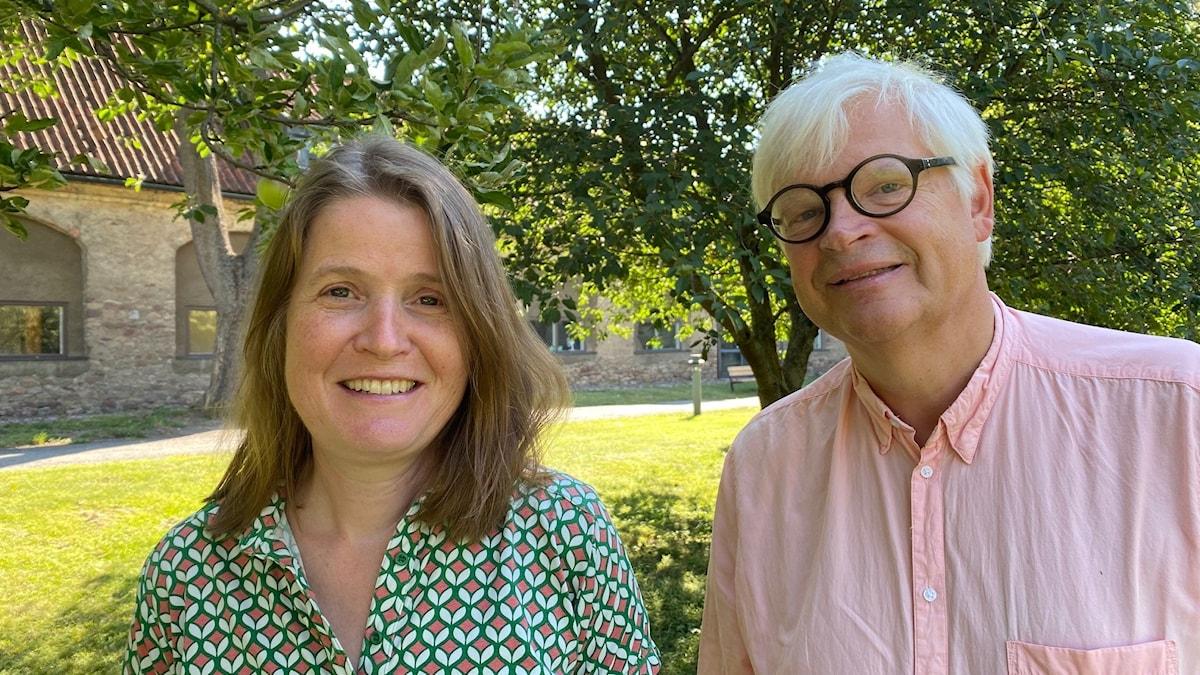 Programledarna Louise Epstein och Thomas Nordegren står under ett äppelträd i Radiohusparken.