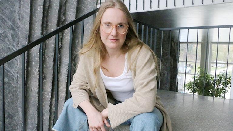 Journalisten Sara Martinsson sitter i en trappa och tittar med bestämd blick in i kameran.