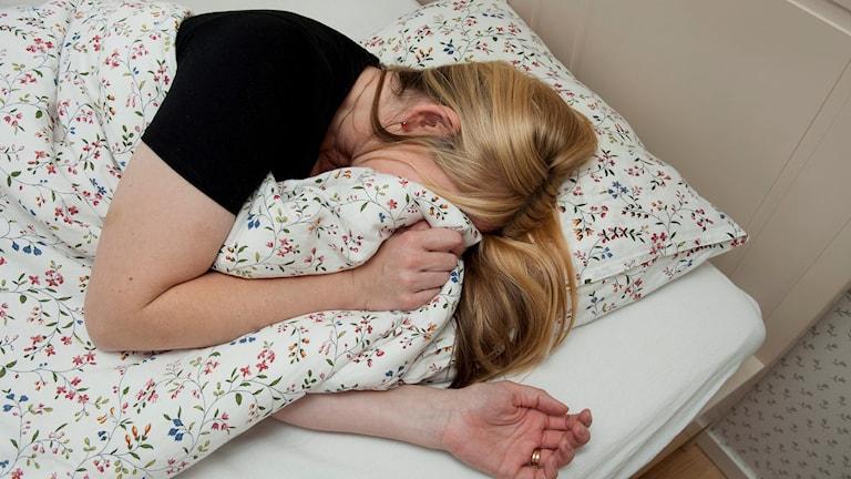 En kvinna ligger i en säng och gömmer ansiktet under täcket
