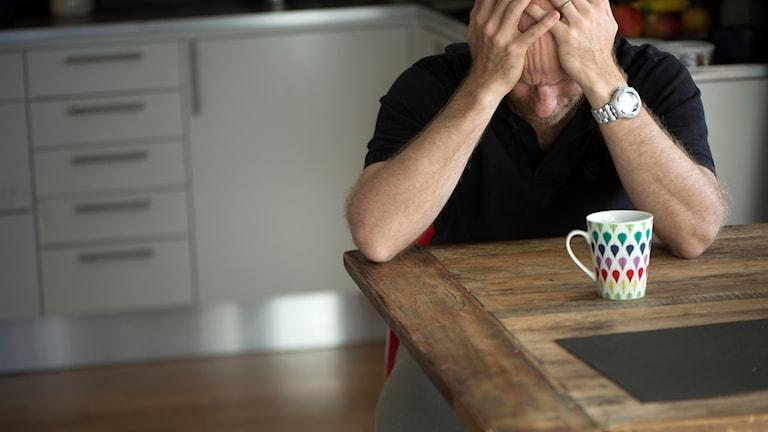 Man som sitter vid ett köksbord och håller händerna på huvudet.