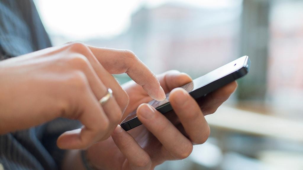 En bild på två händer och en mobiltelefon.