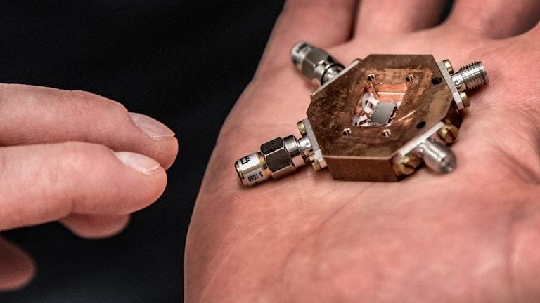 Skruvar och andra delar till en kvantdator, liggandes i en hand.
