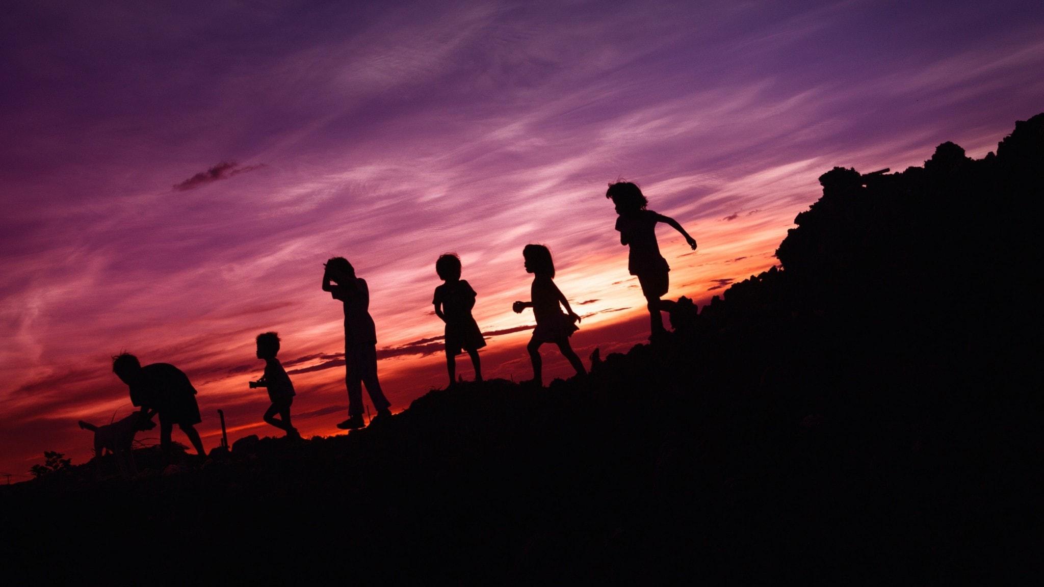 Skuggor av barn i en solnedgång.