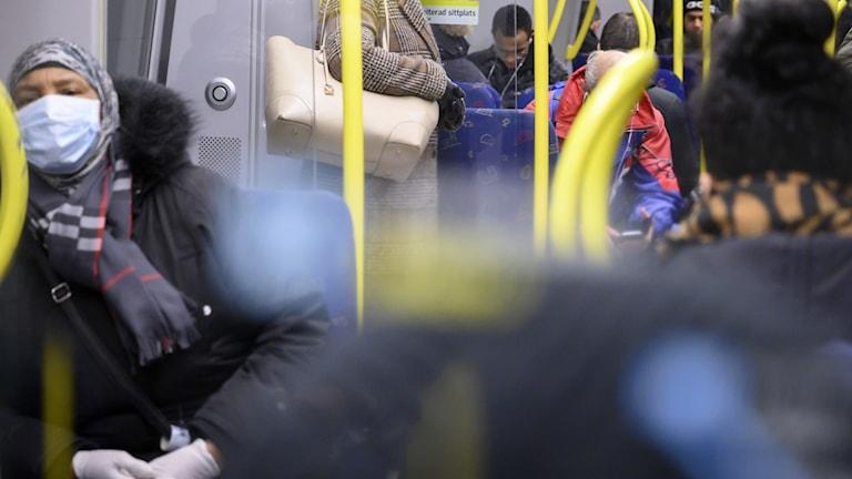 Bild från tunnelbana i Stockholm. En kvinna med munskydd.