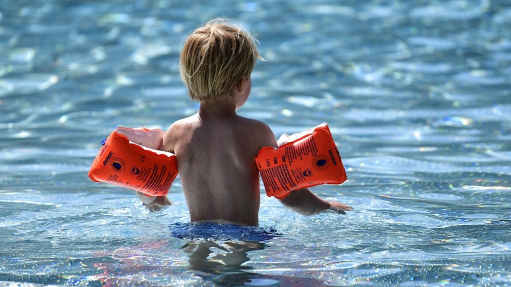 Ett barn med armpuffar i en pool.