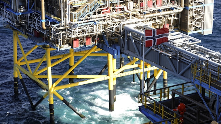 Oljeplattform med norsk flagga och stålrör som reser sig ur havet.