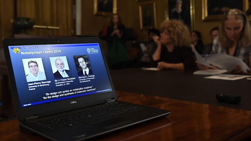 En dator med bild på 2016 års nobelpristagare i kemi; Jean-Pierre Sauvage, Sir J. Fraser Stoddart och Bernard L. Feringa
