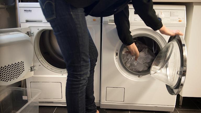 En kvinna fyller tvättmaskinen med smutsig tvätt.