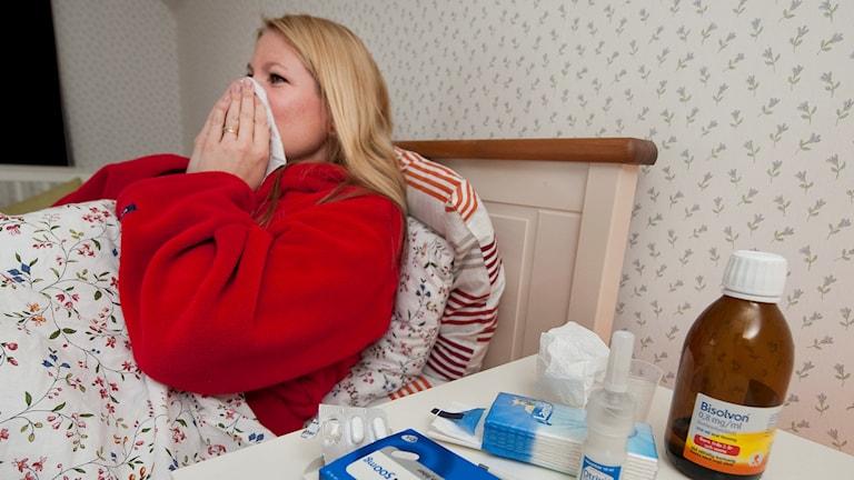 Kvinna ligger i sängen med tabletter och hostmedicin på bord