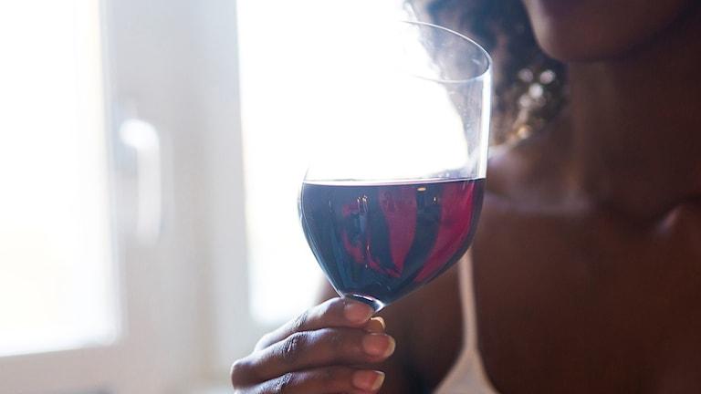 Kvinna dricker ett glas rödvin.