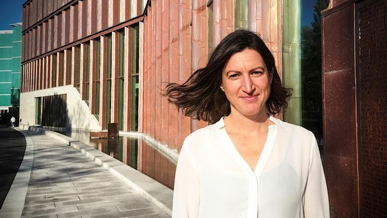 Porträttbild på forskaren Lisa Flower när hon står i soligt väder utanför en byggnad.
