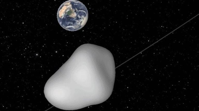 Ljusgrå stenbumling kommer farande i svarta rymden. Jorden på avstånd i bakgrunden.
