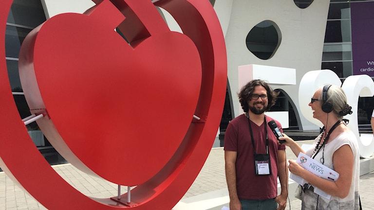 Annika Östman och kardiologen Joel Hernandez bredvid hjärtformad symbol