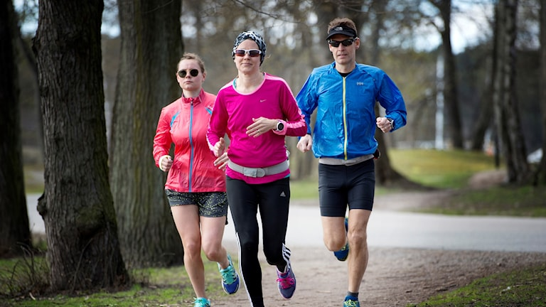 Tre personer i full löparmundering springer tillsammans i en park.