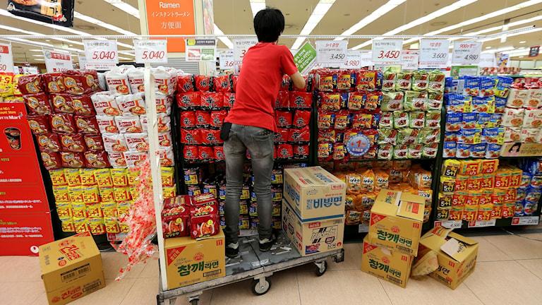 En butiksarbetare plockar upp snabbnudlar på hyllorna i en mataffär i Sydkorea.