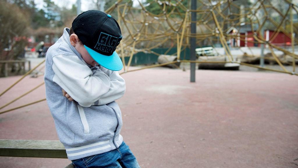 Ledsen pojke på lekplats