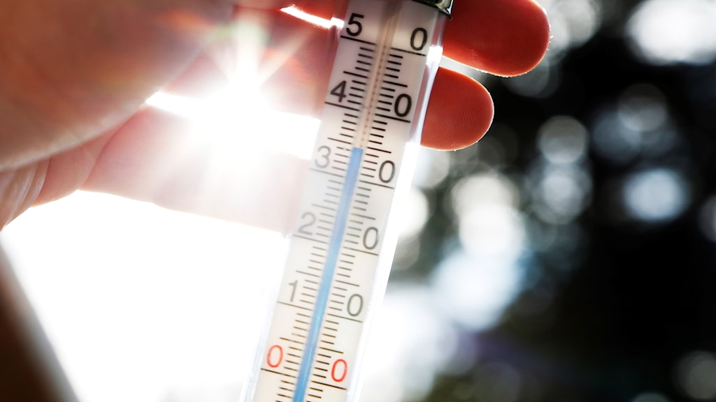 Hand håller termometer som visar över 30 grader, bilden tagen i motljus mot sol.
