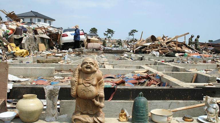 Buddhafigur vid ett sönderrasat hus