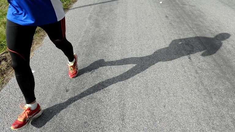 En person i löparskor och löparbyxor springer på en grusväg.