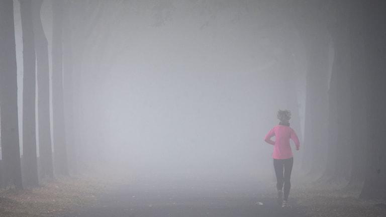 En kvinna som springer genom en dimmig allé