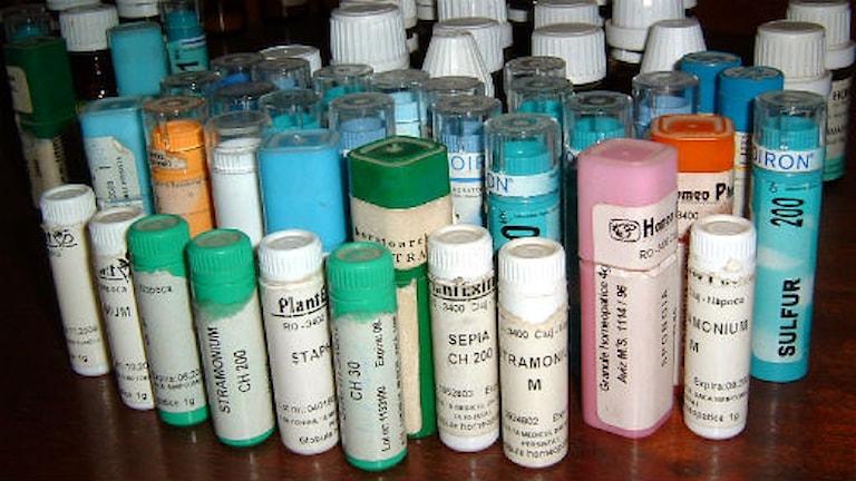 Många små burkar med olika homeopatiska preparat står tillsammans på ett bord. Foto: Wikimedia Commons.