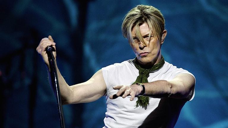Artisten David Bowie på scen med mikrofon.