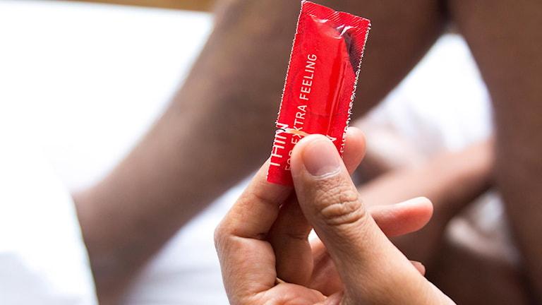 Man i säng håller i förpackning med en kondom.