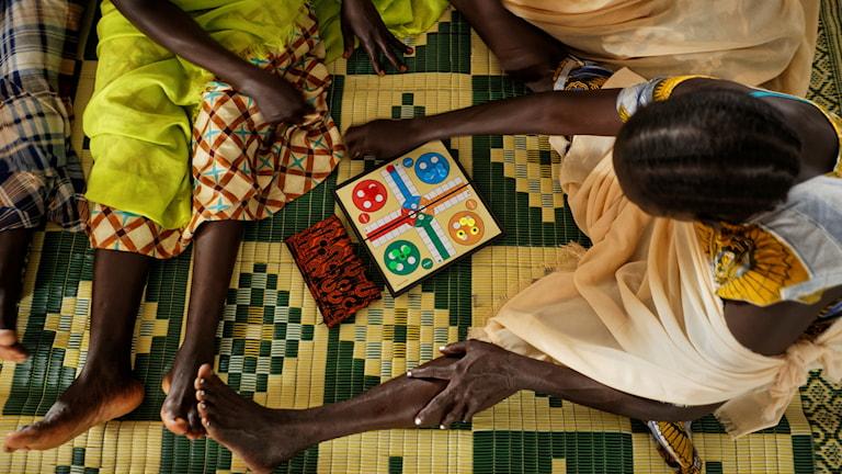 Bild uppifrån visar några kvinnor som spelar ett brädspel.
