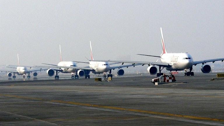 Fyra flygplan i rad taxar ut för att lyfta på flygplatsen i Dubai.