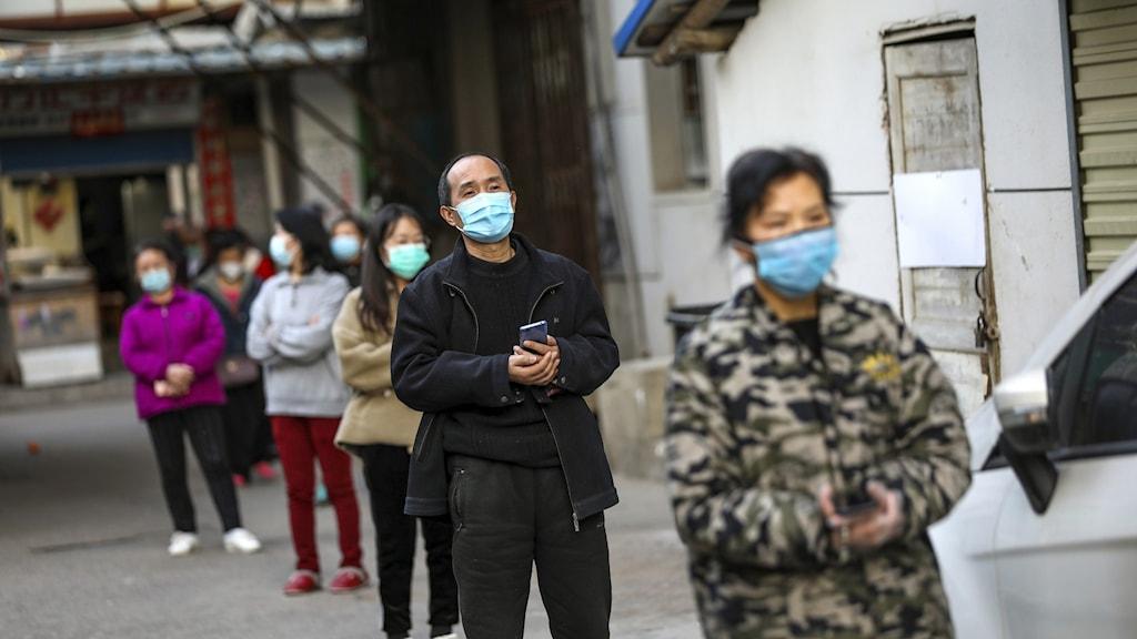 Personer med munskydd står i kö.