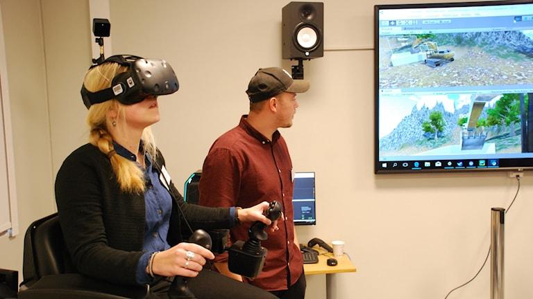 En kvinna har VR-glasögon på sig. En man kollar samtidigt på en skärm.