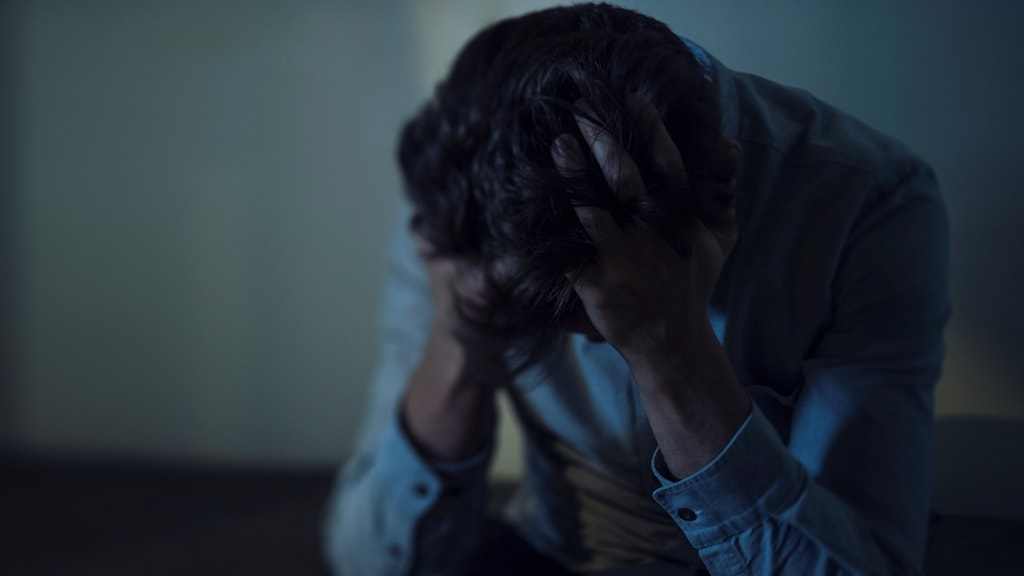 Person sitter i mörkt rum, med händerna för ansiktet.