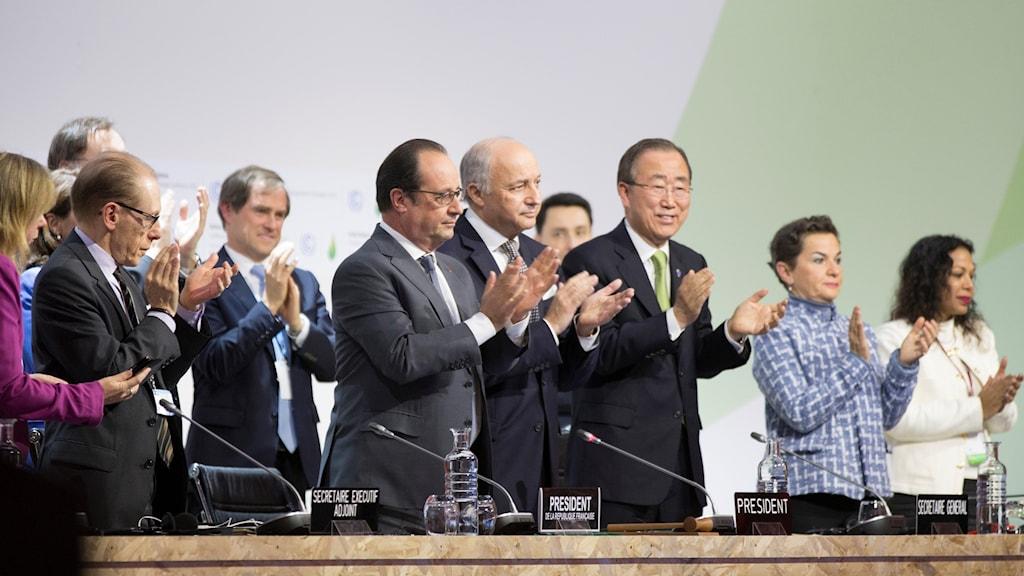 deltagare i klimatmötet i Paris står upp och applåderar