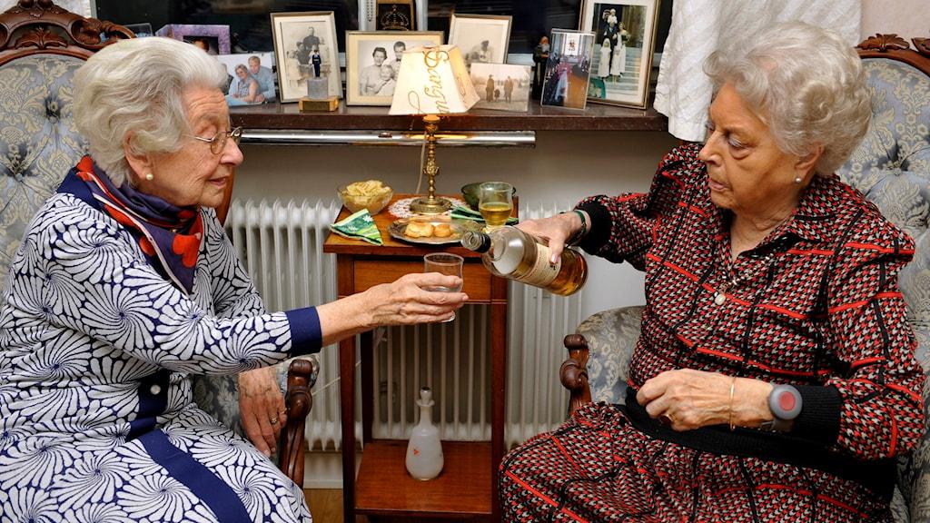 Två äldre vithåriga damer tar en whisky före maten.