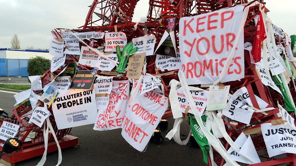 Plakat med klimatbudskap fästade vid en röd modell av eiffeltornet.