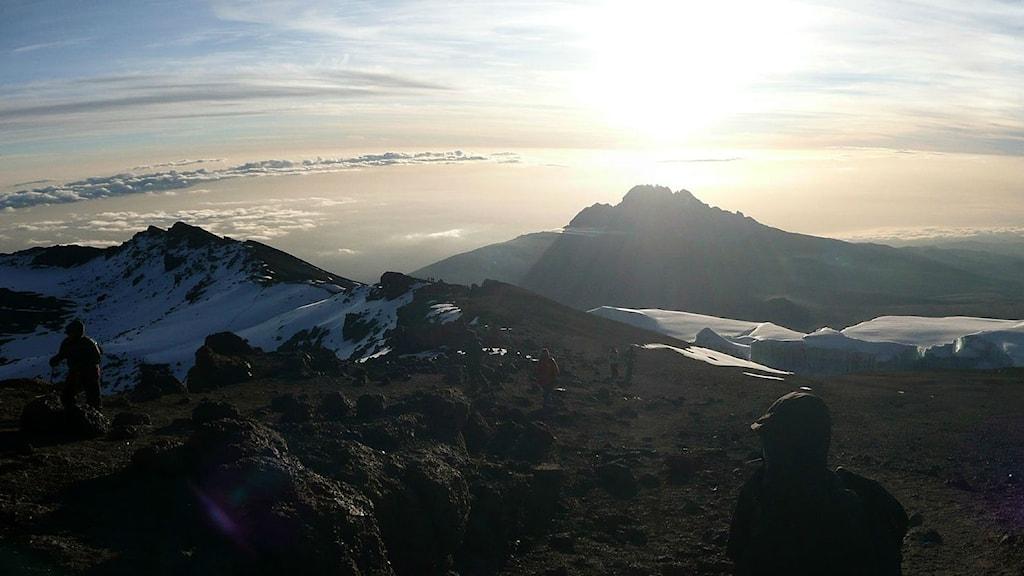 Bild uppifrån Kilimanjaro med bergsbestigare i motljus