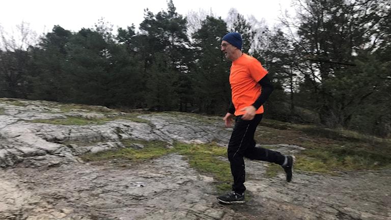 Reporter Tomas Lindblad springer över en klipphäll.